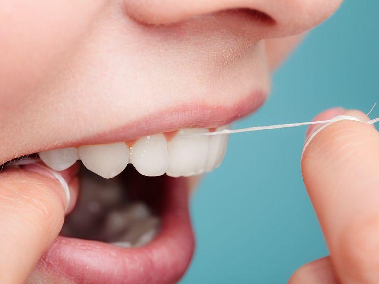 Bạn dùng chỉ nha khoa để lấy hết mảng bám trong răng sau khi ăn