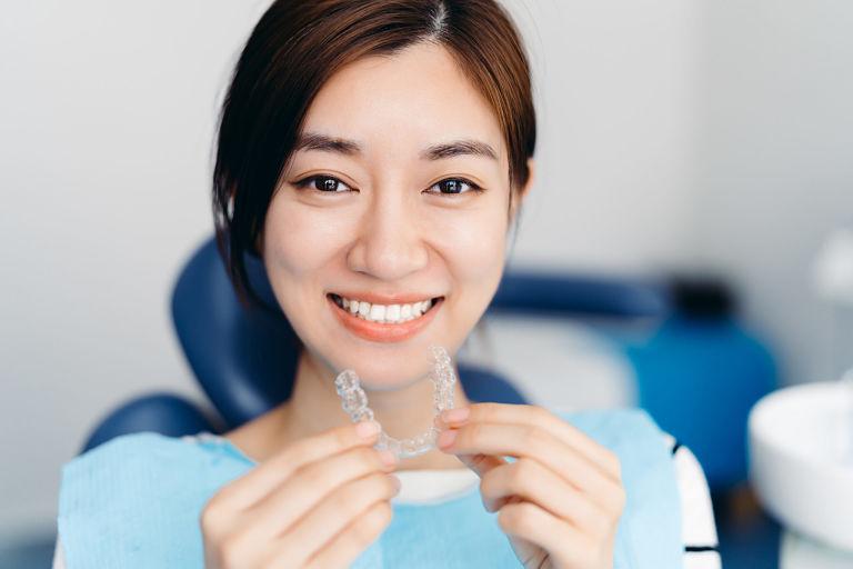 Niềng răng tháo lắp trong suốt sử dụng các khay niềng để dịch chuyển răng